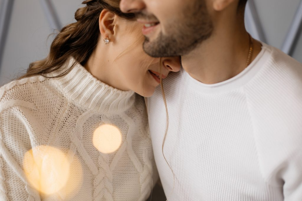 Charming young couple in cozy white home clothes poses in a room